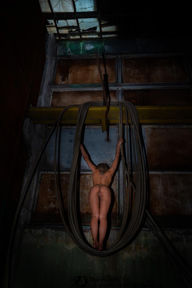 Nude Prisoner Hanging on the Dark Hose Swing